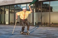 Grand-père espiègle sur une planche à roulettes images libres de droits