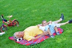 Grand-père et enfant en parc utilisant le comprimé Images libres de droits