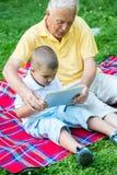 Grand-père et enfant en parc utilisant le comprimé Photographie stock