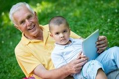 Grand-père et enfant en parc utilisant le comprimé Photos stock