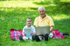 Grand-père et enfant en parc utilisant le comprimé Photographie stock libre de droits