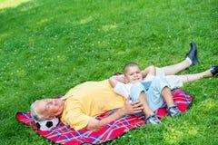 Grand-père et enfant en parc utilisant le comprimé Photos libres de droits