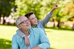 Grand-père et garçon dirigeant le doigt au parc d'été Photographie stock libre de droits