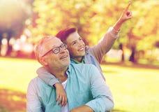 Grand-père et garçon dirigeant le doigt au parc d'été Image stock