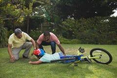 Grand-père et père aidant le garçon tombé avec la bicyclette Image libre de droits