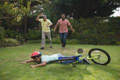 Grand-père et père courant vers le garçon tombé avec la bicyclette Photos stock