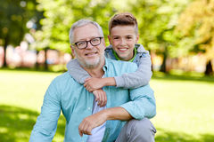 Grand-père et petit-fils étreignant au parc d'été Images stock