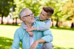 Grand-père et petit-fils étreignant au parc d'été Photographie stock libre de droits