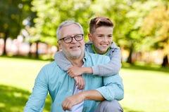 Grand-père et petit-fils étreignant au parc d'été Photo libre de droits
