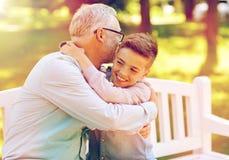 Grand-père et petit-fils étreignant au parc d'été Images libres de droits