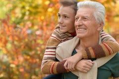 Grand-père et petit-fils étreignant en parc Images libres de droits