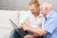 Grand-père et petit-fils avec l'ordinateur portable Photographie stock libre de droits