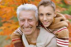 Grand-père et petit-fils en parc automnal Image libre de droits