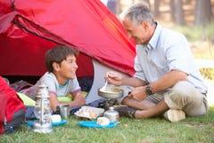 Grand-père et petit-fils faisant cuire le petit déjeuner des vacances de camping Photos stock
