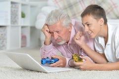 Grand-père et petit-fils jouant des jeux d'ordinateur Photos stock