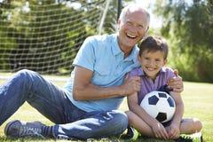 Grand-père et petit-fils jouant le football dans le jardin photos stock