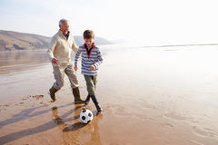 Grand-père et petit-fils jouant le football sur la plage d'hiver Images stock