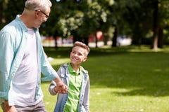 Grand-père et petit-fils marchant au parc d'été Photographie stock libre de droits