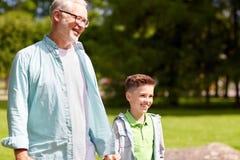 Grand-père et petit-fils marchant au parc d'été Images stock