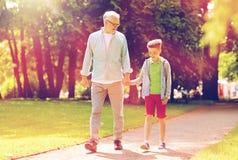 Grand-père et petit-fils marchant au parc d'été Photographie stock
