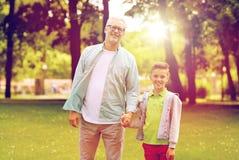 Grand-père et petit-fils marchant au parc d'été Photos stock