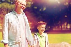 Grand-père et petit-fils marchant au parc d'été Image stock