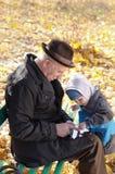 Grand-père et petit-fils partageant un Tablette-PC Photo libre de droits