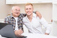 Grand-père et petit-fils s'asseyant avec l'ordinateur portable Images stock