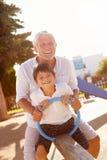 Grand-père et petit-fils sur la bascule dans le terrain de jeu Photo libre de droits