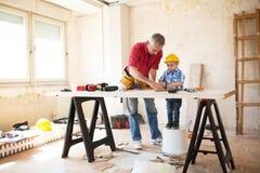Grand-père et petit-fils travaillant avec du bois Photographie stock