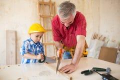 Grand-père et petit-fils travaillant avec du bois dans un garage Image libre de droits