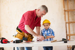 Grand-père et petit-fils travaillant avec du bois dans un garage Images libres de droits