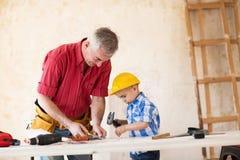 Grand-père et petit-fils travaillant avec du bois dans un garage Photos stock