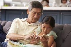 Grand-père et petite-fille à l'aide du téléphone portable à la maison Image libre de droits