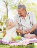 Grand-père et petite-fille colorant des oeufs de pâques sur la couverture à Photo stock