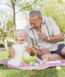 Grand-père et petite-fille colorant des oeufs de pâques sur la couverture à Photographie stock