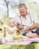 Grand-père et petite-fille colorant des oeufs de pâques sur la couverture à Photo libre de droits