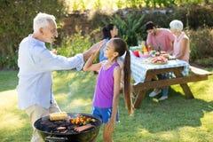 Grand-père et petite-fille donnant de hauts cinq tout en préparant le barbecue Photo stock