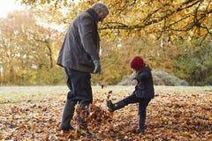 Grand-père et petite-fille donnant un coup de pied des feuilles sur Autumn Walk Image libre de droits