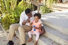 Grand-père et petite-fille jouant avec des bulles ensemble Photographie stock