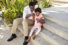 Grand-père et petite-fille jouant avec des bulles ensemble Photos stock