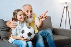 Grand-père et petite-fille riant du moment drôle pendant le football Image libre de droits