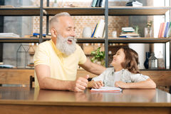 Grand-père et petite-fille riant heureusement à la table Photo stock