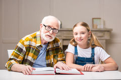 Grand-père et petite-fille s'asseyant à la table avec le livre Images libres de droits