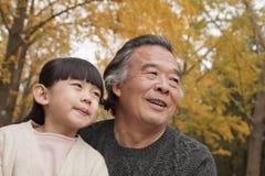 Grand-père et petite-fille souriant et regardant loin en parc Image libre de droits