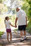 Grand-père et petite-fille tenant des mains tout en marchant Images libres de droits