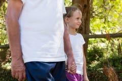 Grand-père et petite-fille tenant des mains tout en marchant Images stock