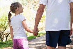 Grand-père et petite-fille tenant des mains tout en marchant ensemble Photos stock