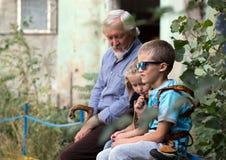 Grand-père et petits-enfants s'asseyant et parlant Photo stock