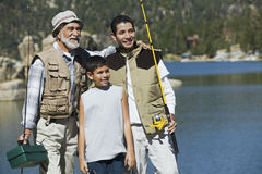 Grand-père et petits-fils avec cannes à pêche par le lac Photo stock